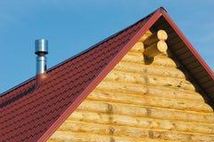 Tapa de la casa de madera del país con la azotea roja Foto de archivo libre de regalías