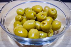 tapa of green olives filled of anchovy in a transparent glass bowl on a table just served to be eaten stock photos