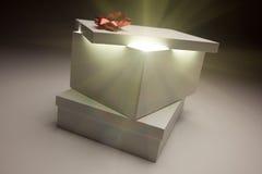 Tapa roja del rectángulo de regalo del arqueamiento que muestra contenido muy brillante Foto de archivo libre de regalías