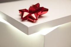 Tapa roja del rectángulo de regalo del arqueamiento que muestra contenido muy brillante Imagen de archivo