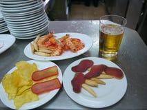 Tapas deliziosi sui piatti bianchi e su un vetro di birra immagini stock