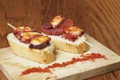 Tapas espagnols classiques : poulpe cuit avec une tranche de pain Images stock