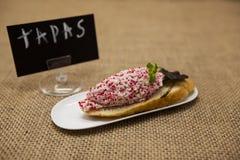 Tapas espanhóis deliciosos do cartaz dos TAPAS com o caranguejo tartare com as ovas e a salada dos peixes de voo em uma fatia de  Foto de Stock Royalty Free