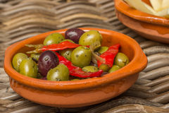 Tapas, marinated olives with red peppers Royalty Free Stock Photos
