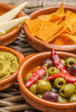 Tapas, marinated olives, tortilla chips, guacamole, manchego Stock Photos
