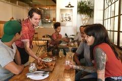 Tapas nouvellement fabriqués servants de sourire de serveur aux clients de sourire de restaurant Photos stock