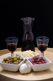 Tapas and red wine. Italian tapas like cheese, olives, sausage, garlic and red wine on a wooden plate stock photos