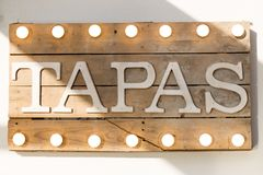 Rustic wooden Tapas board. Tapas sign made of wooden planks and light bulbs on top and bottom Royalty Free Stock Photo
