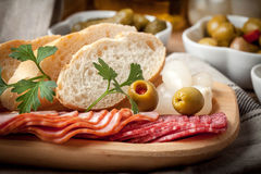 Tapas with sliced sausage, salami, olives, marinated onions, cuc Stock Photography