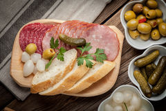 Tapas with sliced sausage, salami, olives, marinated onions, cuc Royalty Free Stock Images