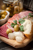 Tapas with sliced sausage, salami, olives, marinated onions, cuc Stock Photos