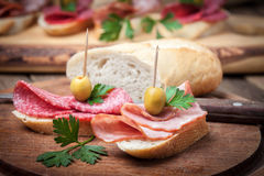 Tapas with sliced sausage, salami, olives and parsley. Royalty Free Stock Photo