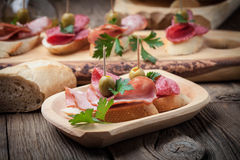 Tapas with sliced sausage, salami, olives and parsley. Stock Images