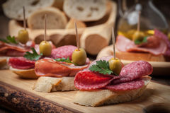 Tapas with sliced sausage, salami, olives and parsley. Stock Photography
