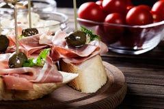 Tapas spagnoli con il serrano del jamon delle fette, il salame, le olive ed i cubi del formaggio su una tavola di legno Fotografie Stock