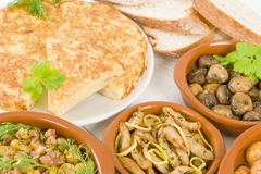 Tapas. Spanish Tortilla - Traditional Spanish omelette made with potatoes and fried in olive oil. Various other tapas on the table Royalty Free Stock Photography