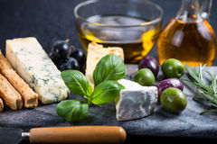 Tapas style cheese selection with olives,grapes and herbs Royalty Free Stock Photos