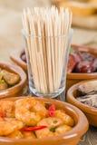 Tapas - Toothpicks. Surrounded by traditional Spanish tapas dishes (gambas pil pil, , pollo al limon con ajo, rollitos de pollo con aceitunas, chorizo al vino Stock Images