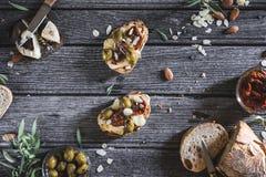 Tapas vegetariani del pane delle mandorle con i pomodori, l'oliva verde, il formaggio e le mandorle secchi per brunch fotografia stock