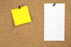 Tape al tablón de anuncios con corcho con el papel de nota amarillo y blanco Imagen de archivo libre de regalías