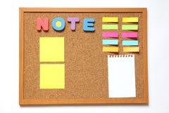 Tape al tablero con corcho con la fraseología de la nota y el papel de nota Imagenes de archivo