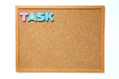 Tape al tablero con corcho con la fraseología de la tarea en el fondo blanco Fotos de archivo libres de regalías