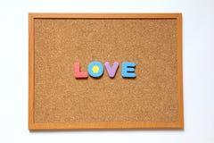 Tape al tablero con corcho con la fraseología del amor en el fondo blanco Imagenes de archivo