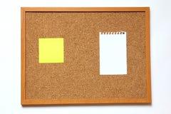 Tape al tablero con corcho con la nota de papel sobre el fondo blanco Fotos de archivo libres de regalías