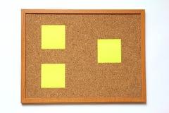 Tape al tablero con corcho con la nota de papel sobre el fondo blanco Imagenes de archivo
