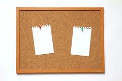 Tape al tablero con corcho con la nota de papel sobre el fondo blanco Imágenes de archivo libres de regalías