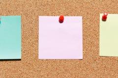 Tape al tablero con corcho con las notas en blanco coloridas y empuje los pernos foto de archivo