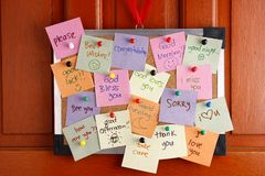 Tape al tablero con corcho con los mensajes en los papeles coloridos y empuje los pernos que cuelgan por una puerta Imagen de archivo