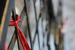 Tape on the bridge. Red ribbon on a bronze bridge Stock Images