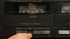 Tape cassette. And man pushing the buttons