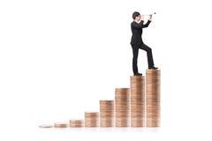 Étape d'homme d'affaires sur l'argent et avec le télescope Photos stock