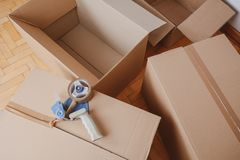Tape dispenser sealing a shipping cardboard box. Indoors stock photos