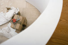 Tape duct dispenser on top of sealed cardboard box, paper and packing foam on floor beside staircase Royalty Free Stock Photo