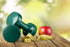 Dumbbells with measuring tape and apple for diet Stock Images