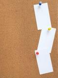 Tape el noticeboard con corcho con tres tarjetas blancas fijadas verticalmente Fotos de archivo