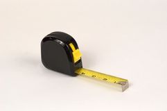 Tape Measure. Large black tape measure with 4 inches of tape extended, tape is yellow with large numbers and locked in place Stock Image