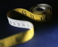 Tape Measure. Shot of yellow tape measure with shallow depth of field stock photos