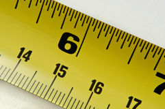 Tape measure. Close up of a section of metal tape measure arranged diagonally across the image with white background Royalty Free Stock Images