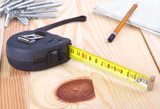 Tape measure. Black tape measure on on wooden board Royalty Free Stock Image