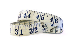 Tape Measure. Studio macro of flexible tape measure against a white background with soft shadows. Copy space royalty free stock images