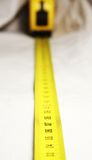 Tape measure. Yellow tape measure on white background royalty free stock photography