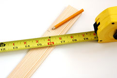Tape measure. Wood and pencil shot against a white background stock image
