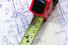Tape measure against blueprints Stock Photos