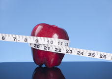 Tape measure and apple. Stock Image