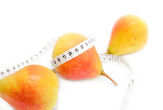 Tape measure around pears. Tape measure wrapped around three ripe pears, healthy eating concept on white background Royalty Free Stock Image