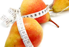 Tape measure around pears. Healthy eating or dieting concept with tape measure wrapped around ripe pears, white background Stock Image